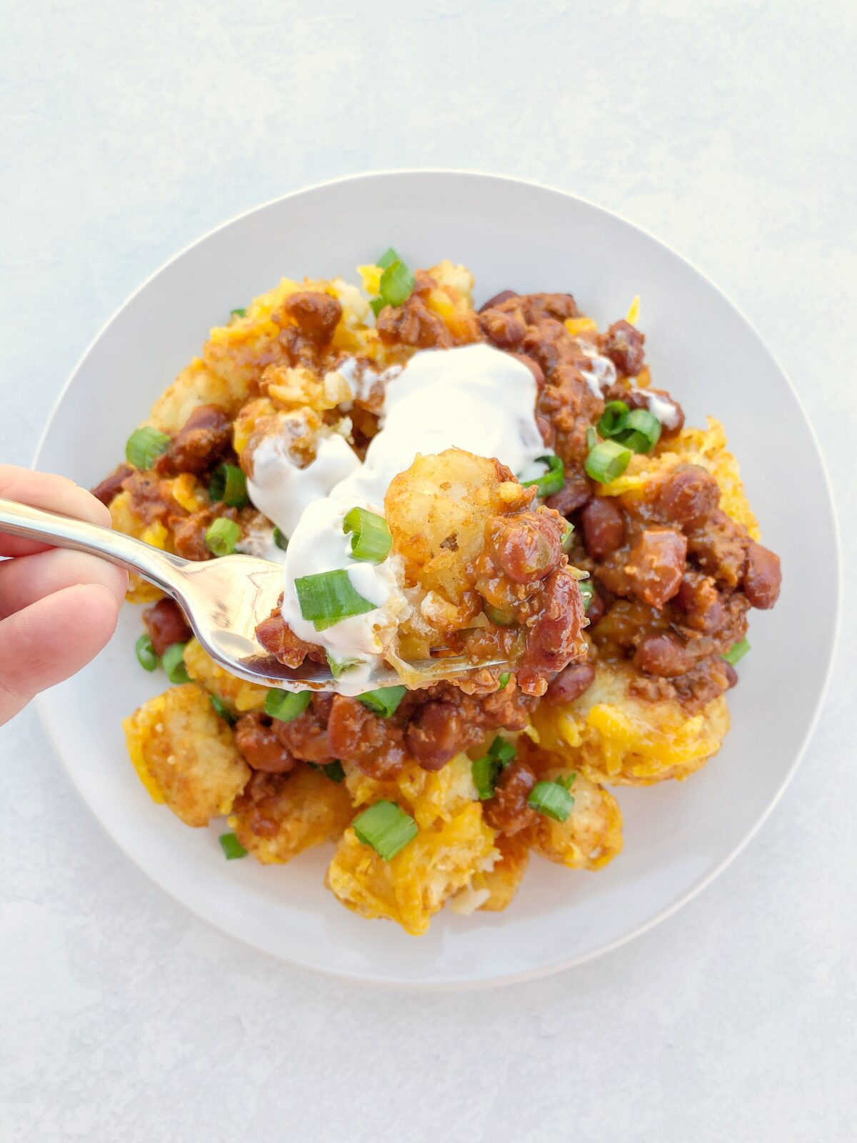 Tater Tot Nachos with dairy free cheese, chili, and sour cream